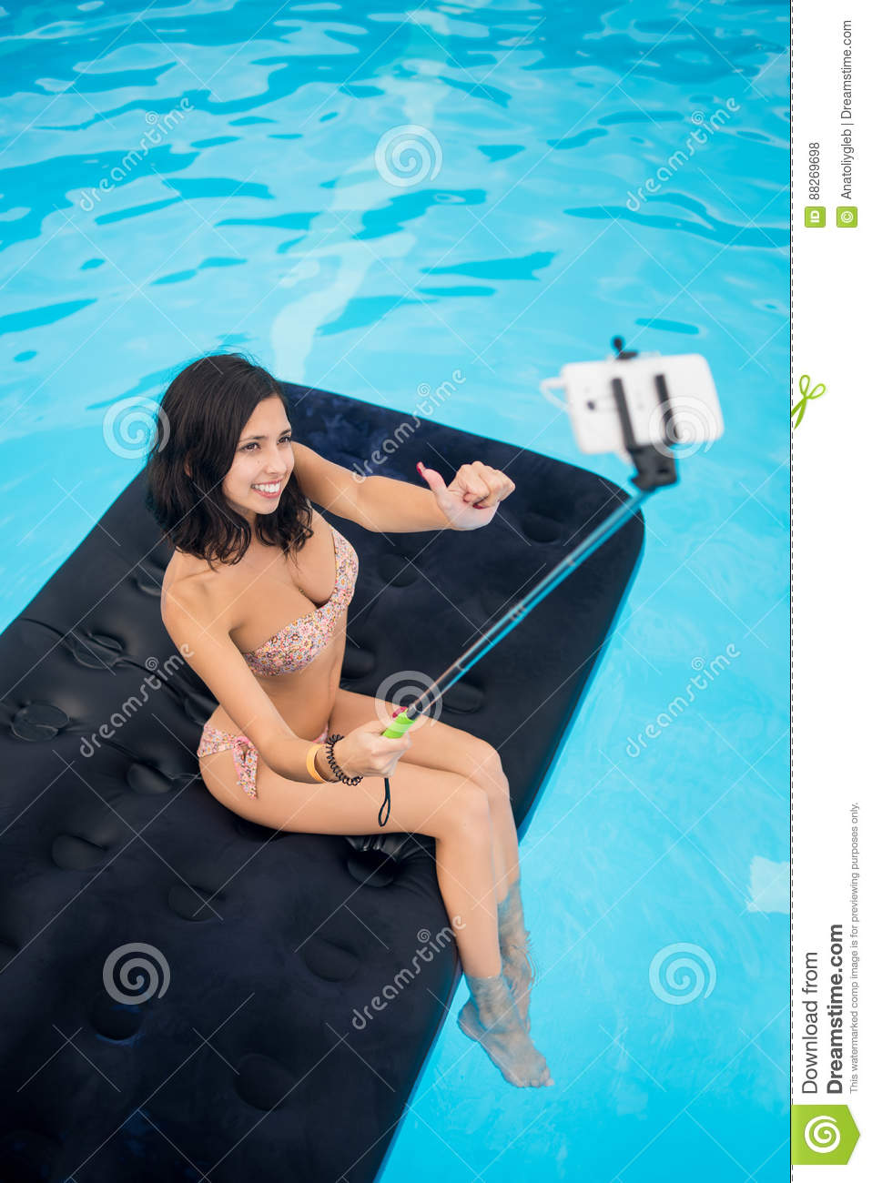 Girl taking selfie photo on the phone with selfie stick and showing thumbs up gesture of good class on mattress in pool
