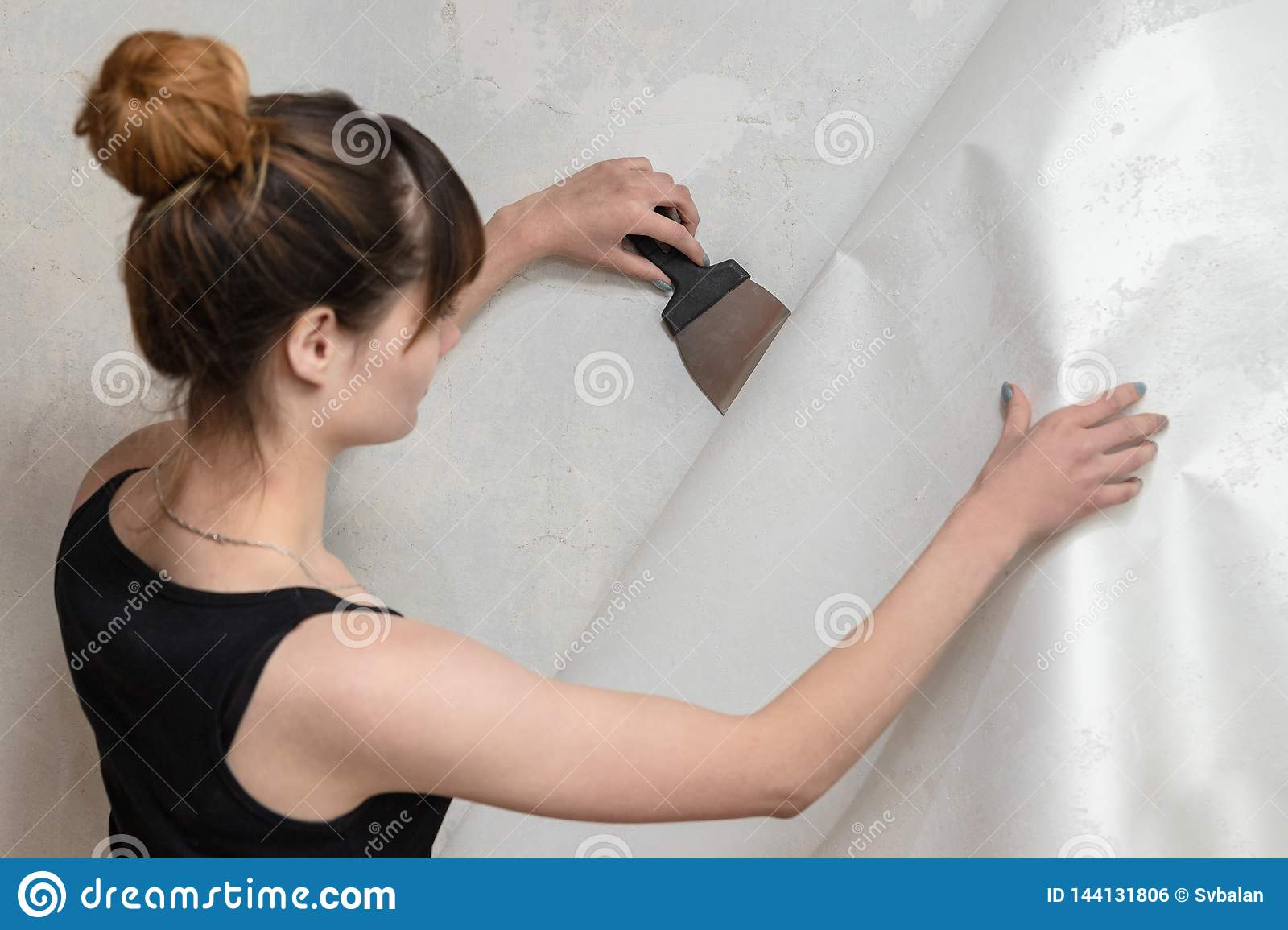 The girl tears off the old wallpaper from the concrete wall and holds a spatula.