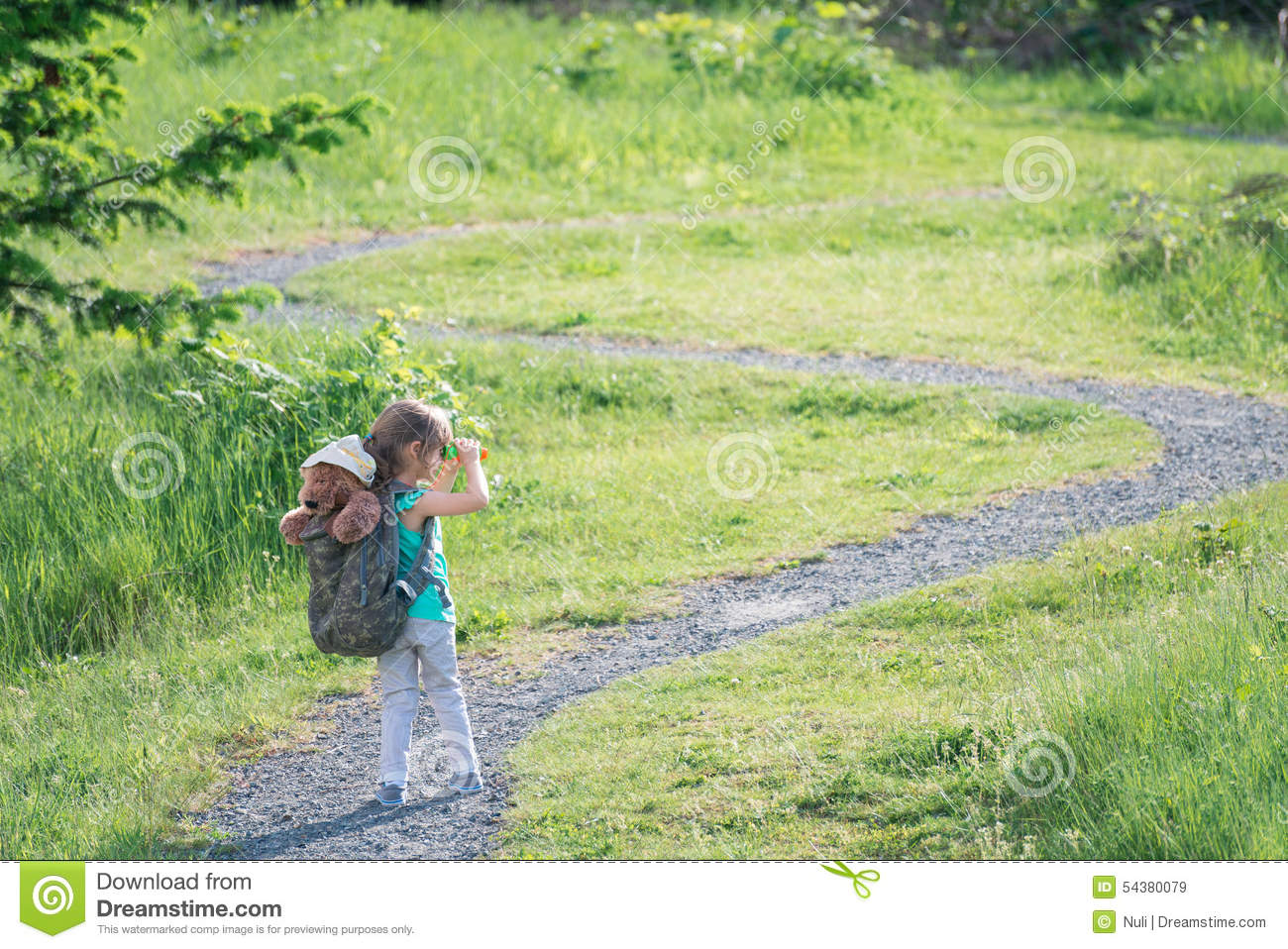 Girl With Teddy Bear In Backpack Looking At The Trail Ahead Stock