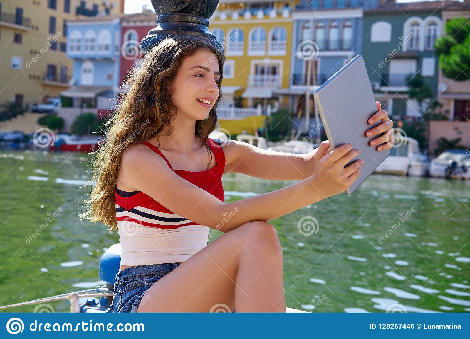 Girl teen with skateboard and tablet selfie