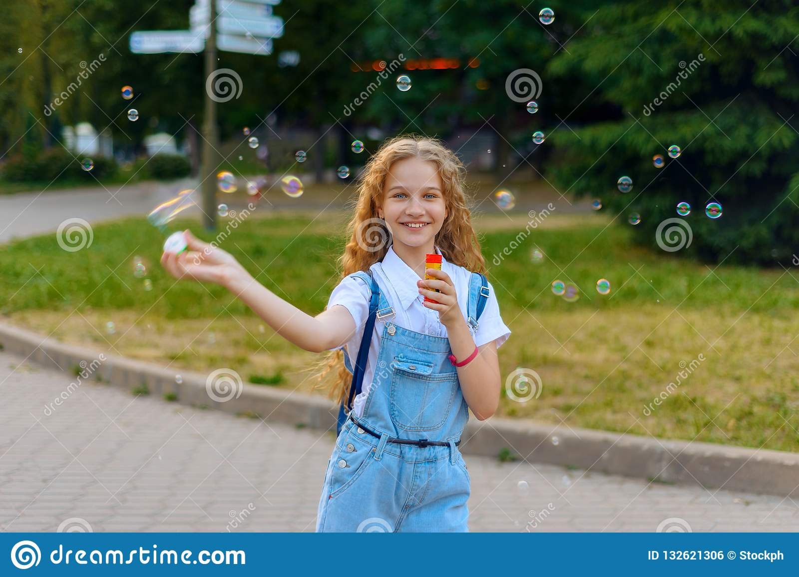 Girl teenager happy smiling blows soap bubbles