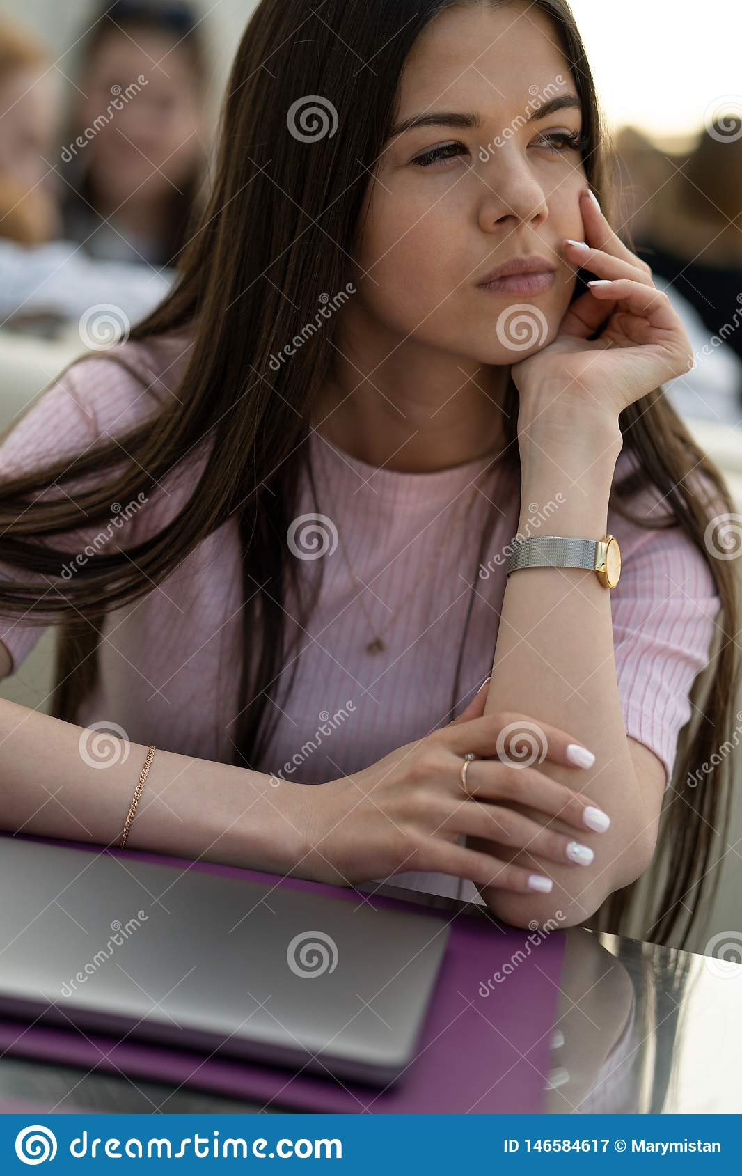 The girl thought in a cafe. In front of the girl is a closed laptop