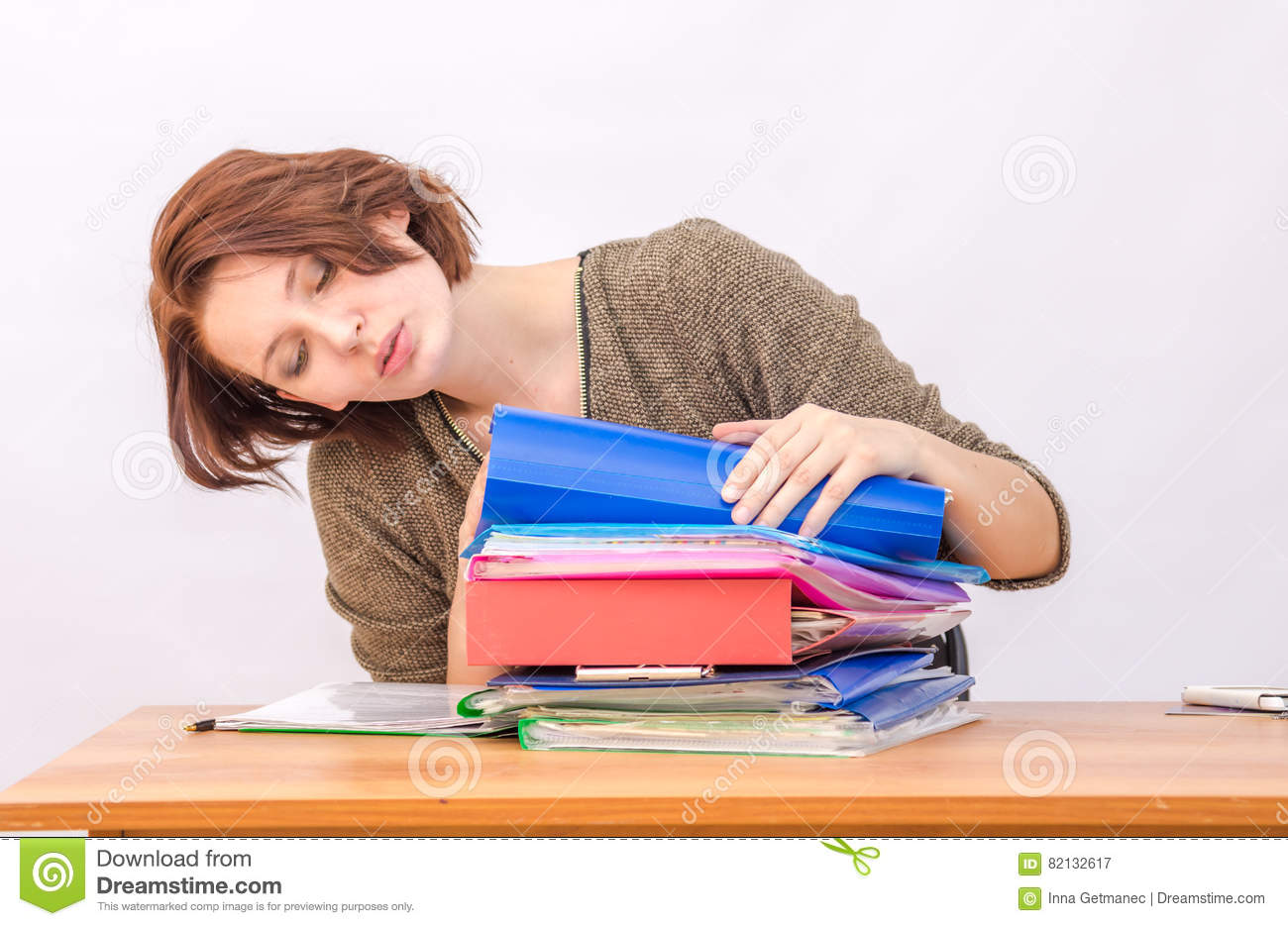 Girl thoughtfully office employee goes through a stack of folders
