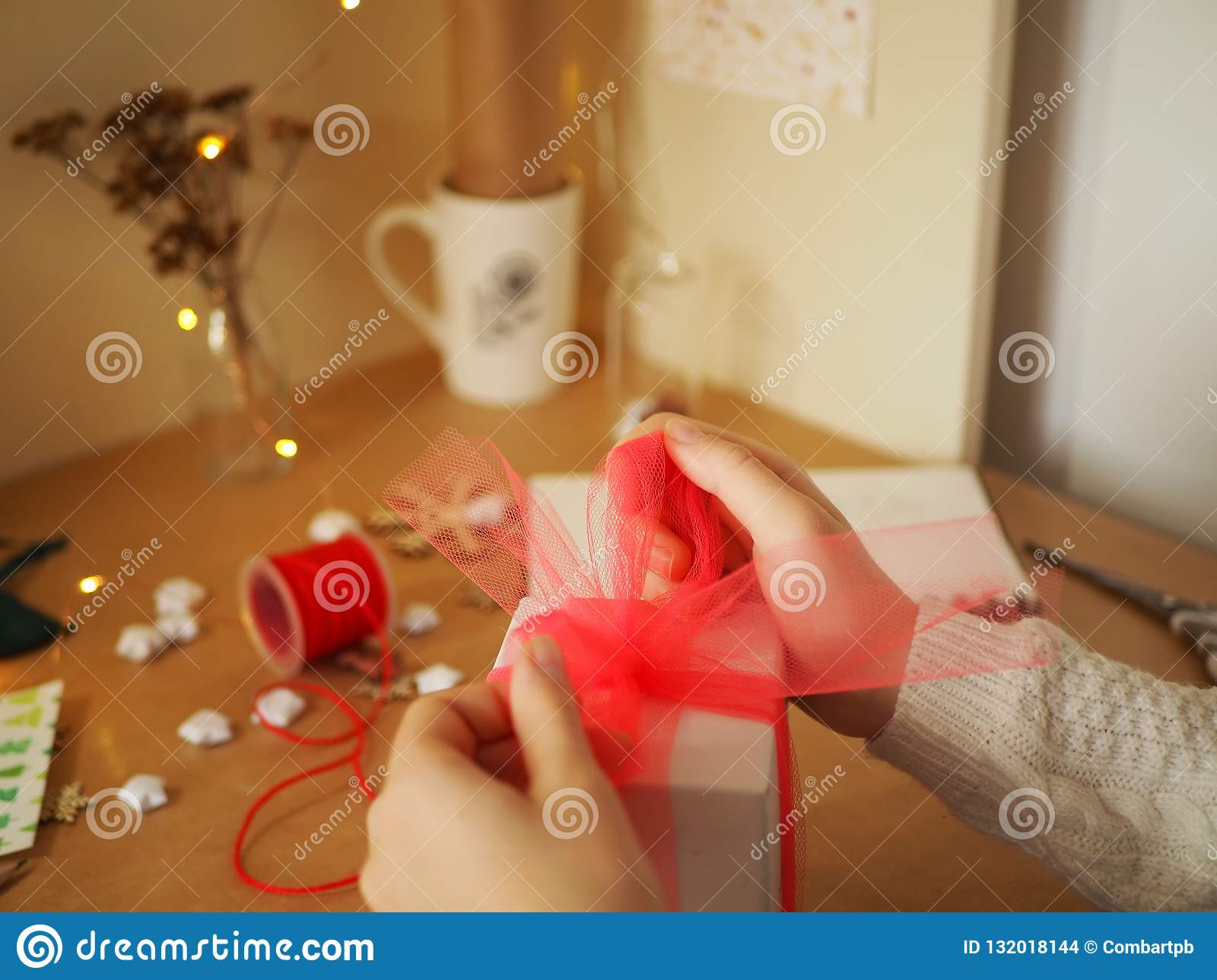 A girl ties a ribbon of tulle on a gift, preparing a surprise