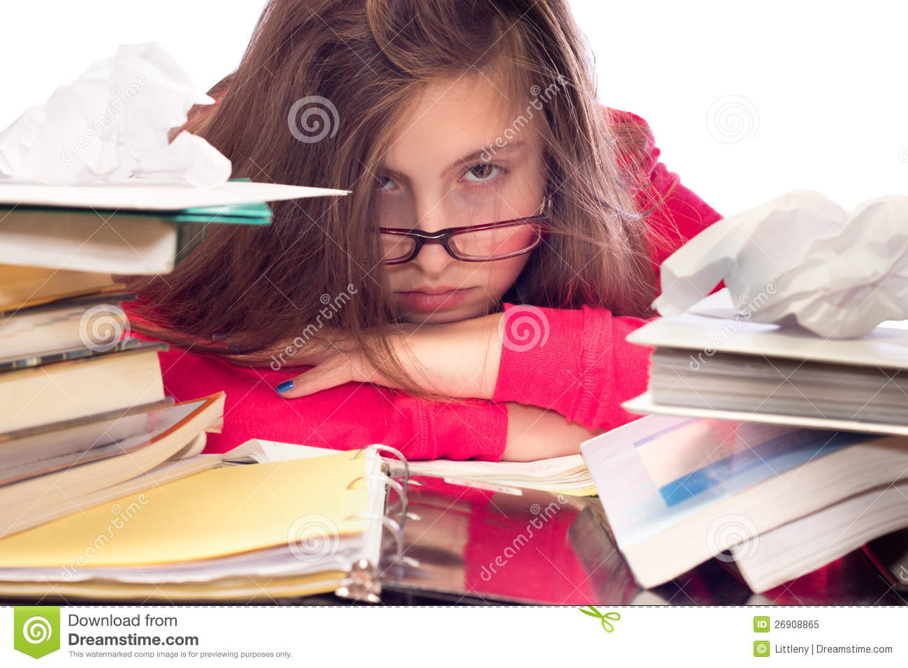 Cute teenage girl with glasses, surrounded by books and school work ...