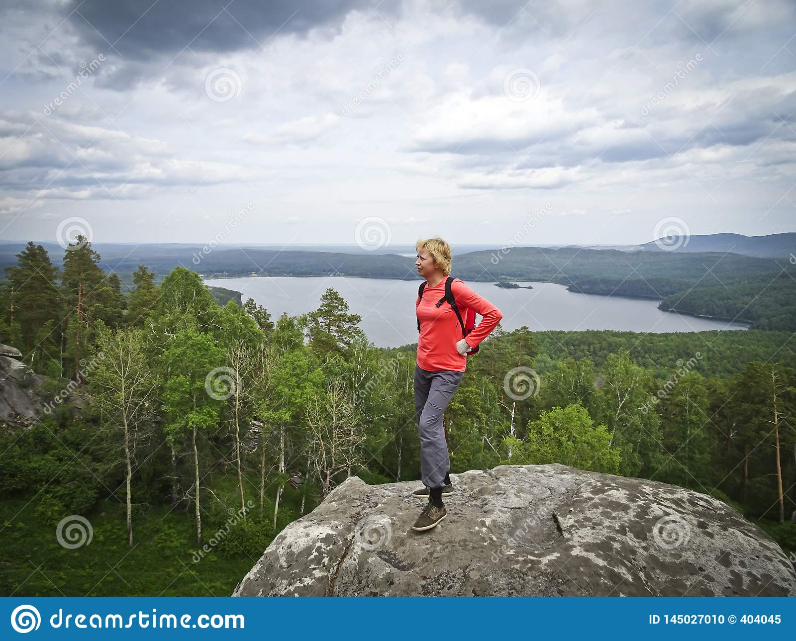 A girl on top of a mountain, in the background of a panorama of mountains and lakes. The girl is happy