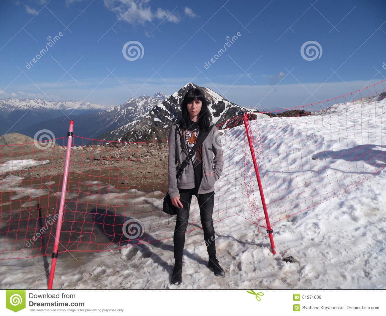 Girl on the top of the mountain, snowy peaks and blue sky