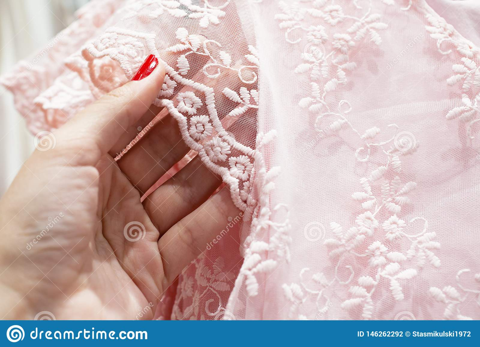 The girl touches the delicate pink lace