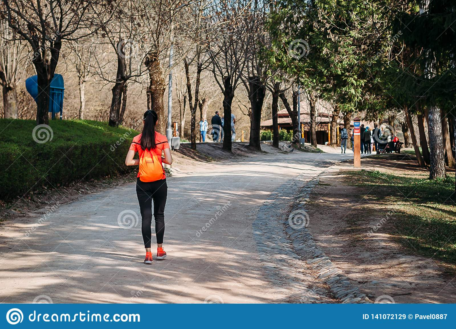 Girl tourist in orange t-shirt walking with backpack in Park on road