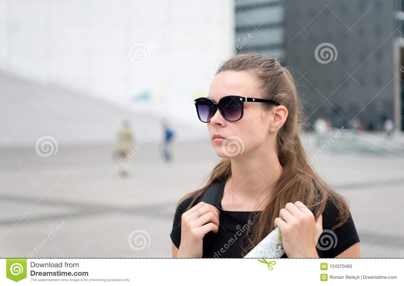 Girl tourist sunglasses enjoy view paris square city center. Woman stand in front of urban architecture copy space. Must