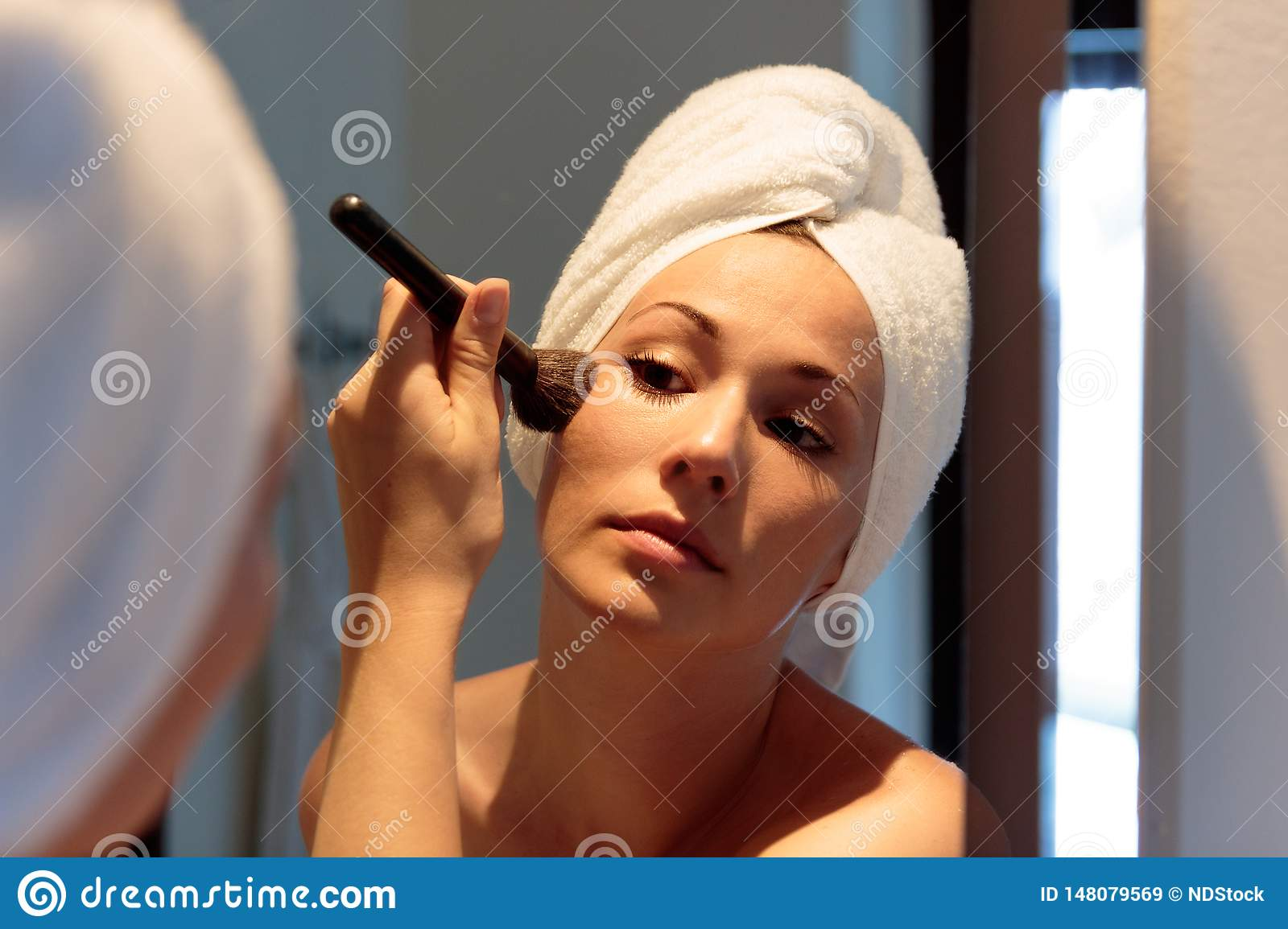Woman in front of the mirror who is putting on make-up before going out at night