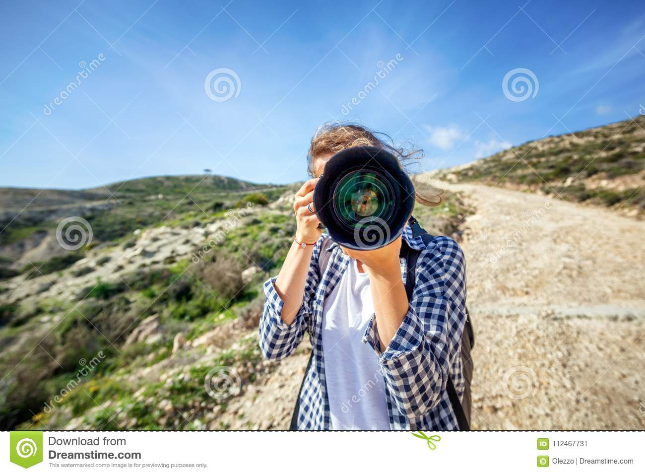 Girl traveler with a camera in hand, against a beautiful summer
