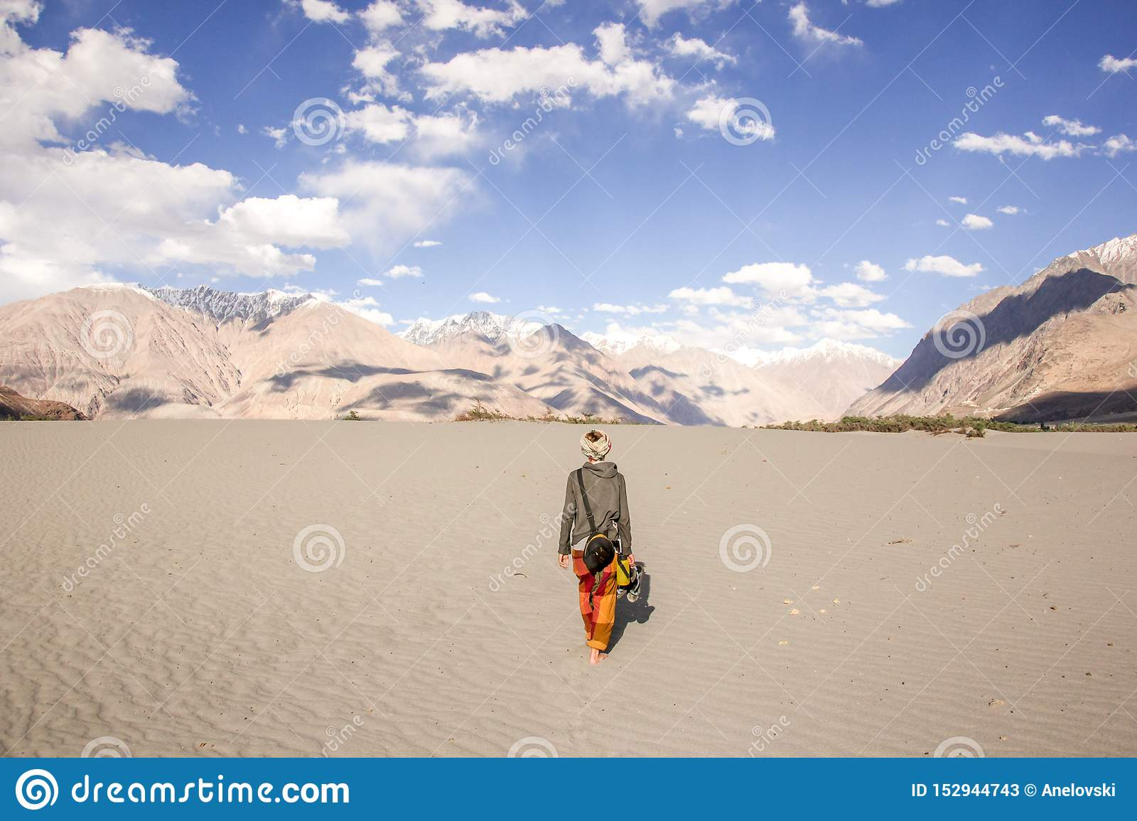 Girl hiking through a desert surrounded by beautiful mountains..