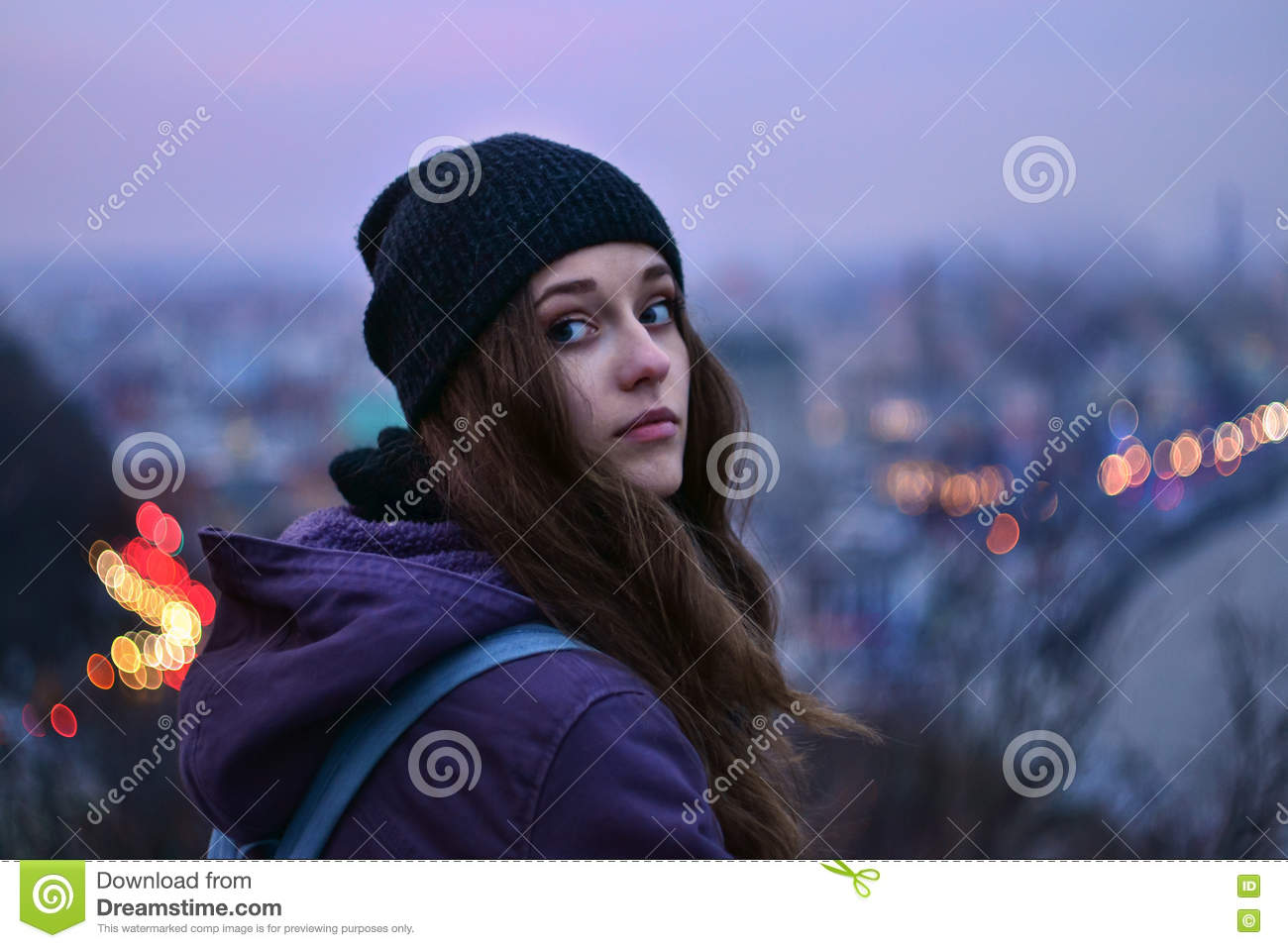 Girl traveler standing in front of winter evening cityscape