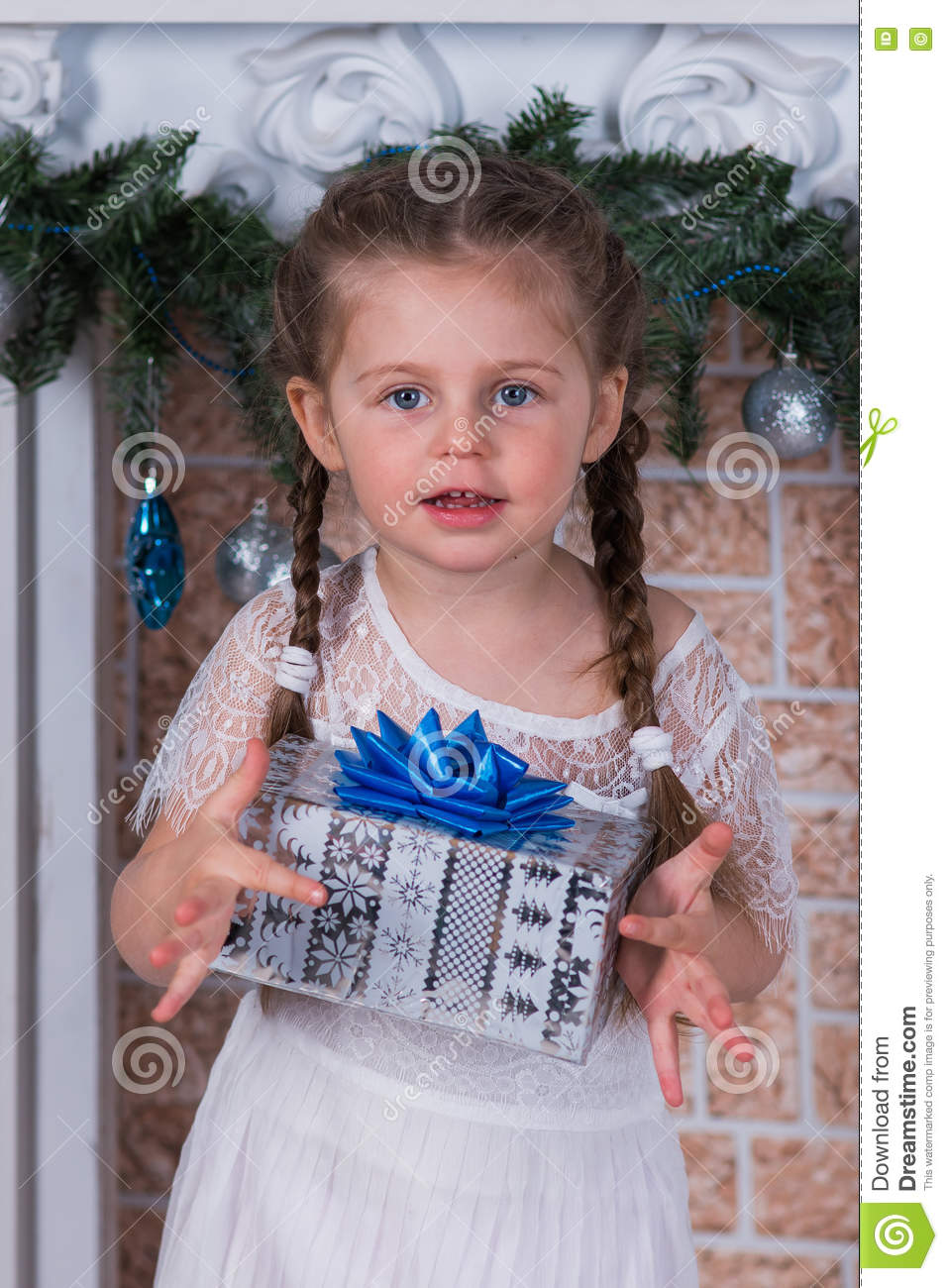 Girl with two pigtails with a gift in a box in the New Years holiday