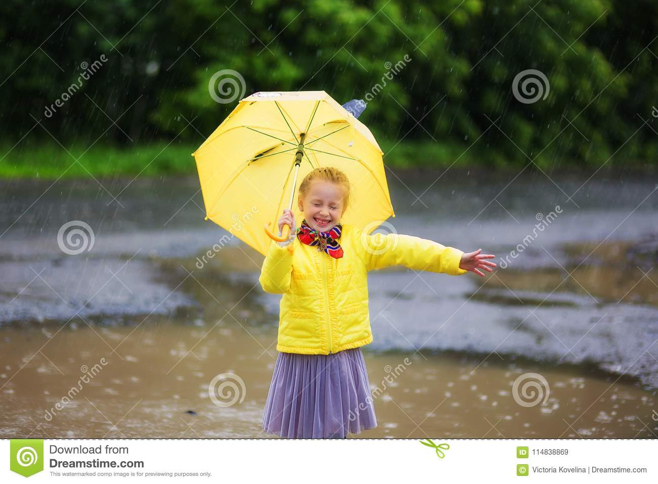 Little little girl in a yellow jacket and yellow boots with yellow umbrella in the rain.