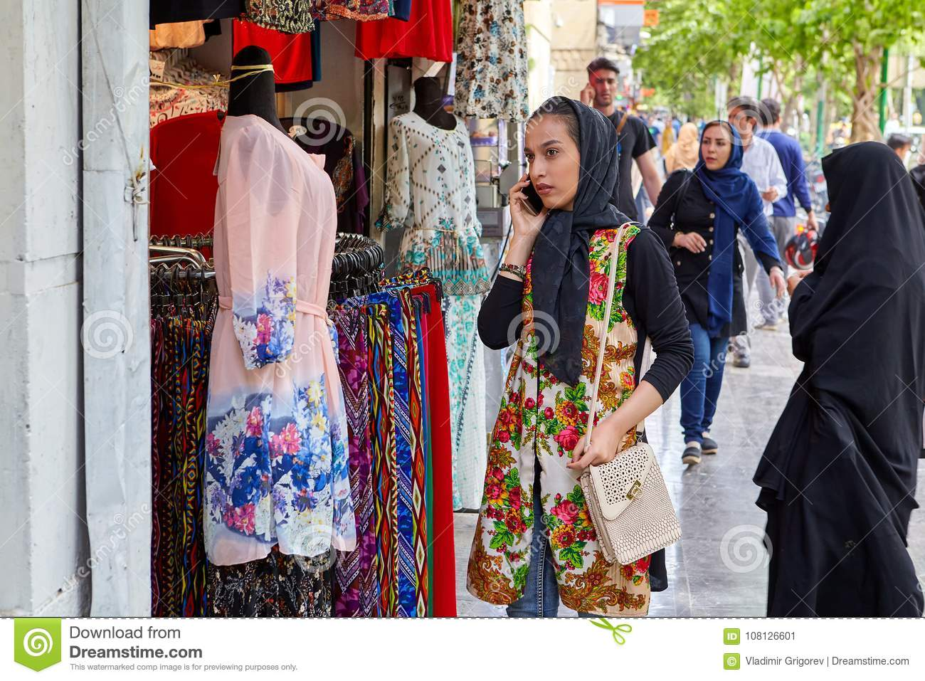 6810ed2ad3e3 Girl Uses Smartphone Near Shop With Bright Clothes