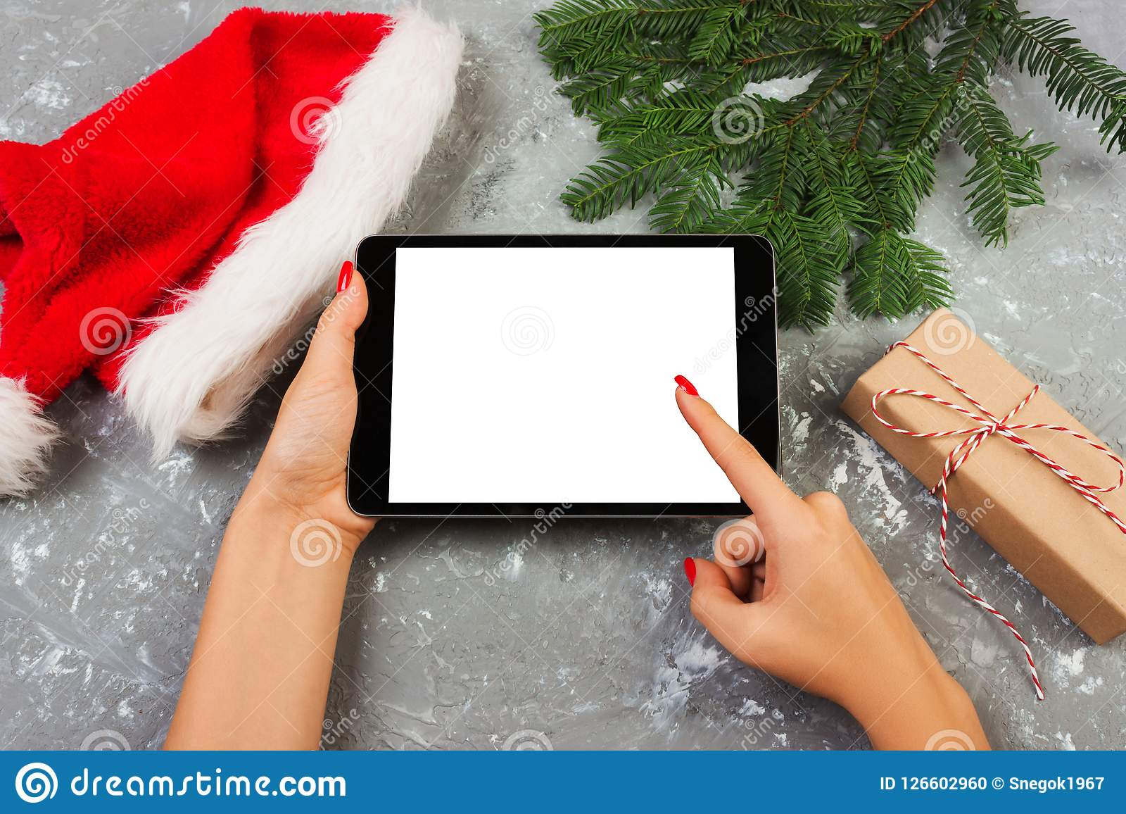 Girl using tablet technology in home, person holding computer on background Christmas decoration, female hands texting, mockup tem