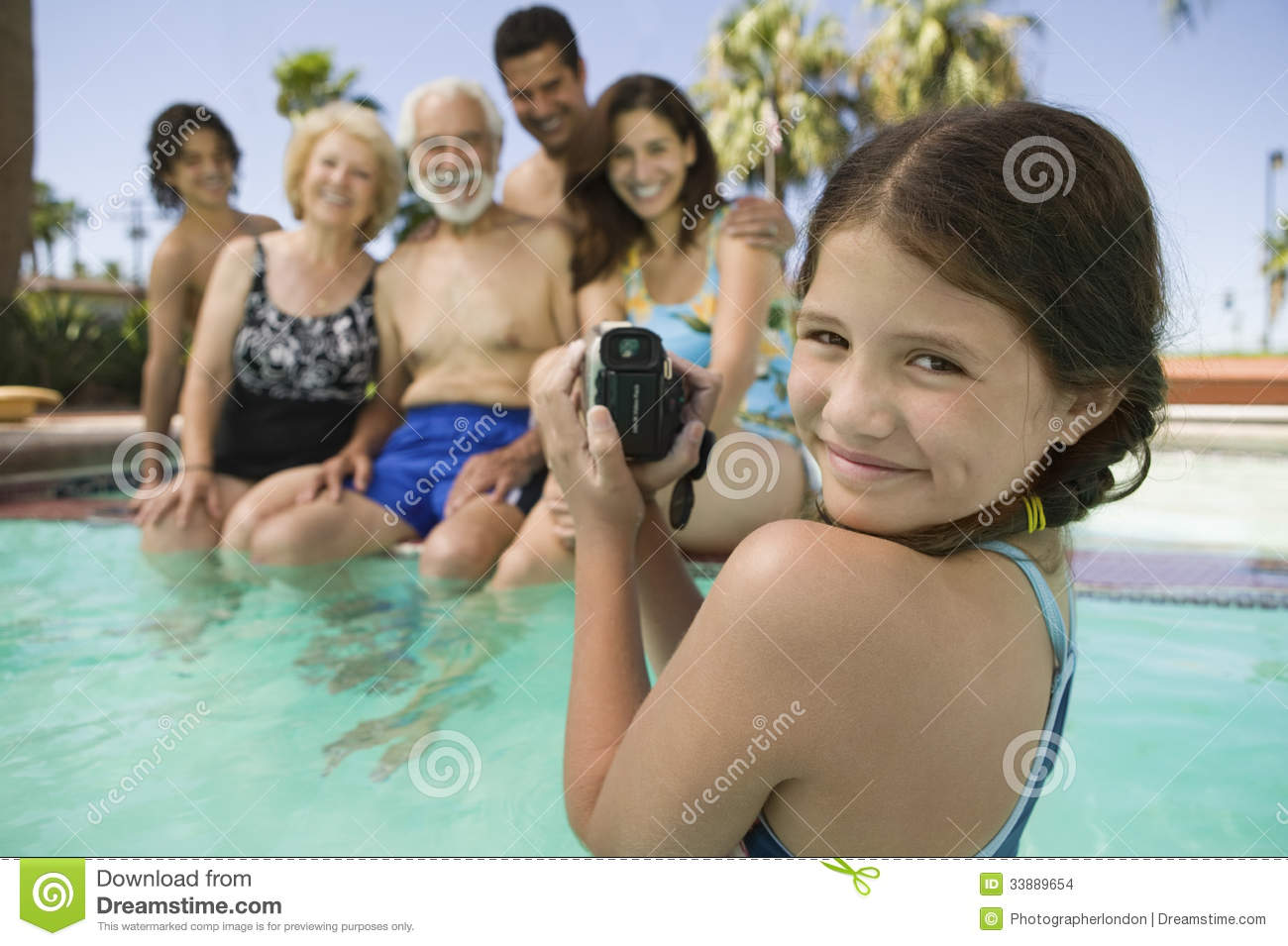 Girl with video camera recording family in swimming pool for Family swimming pool