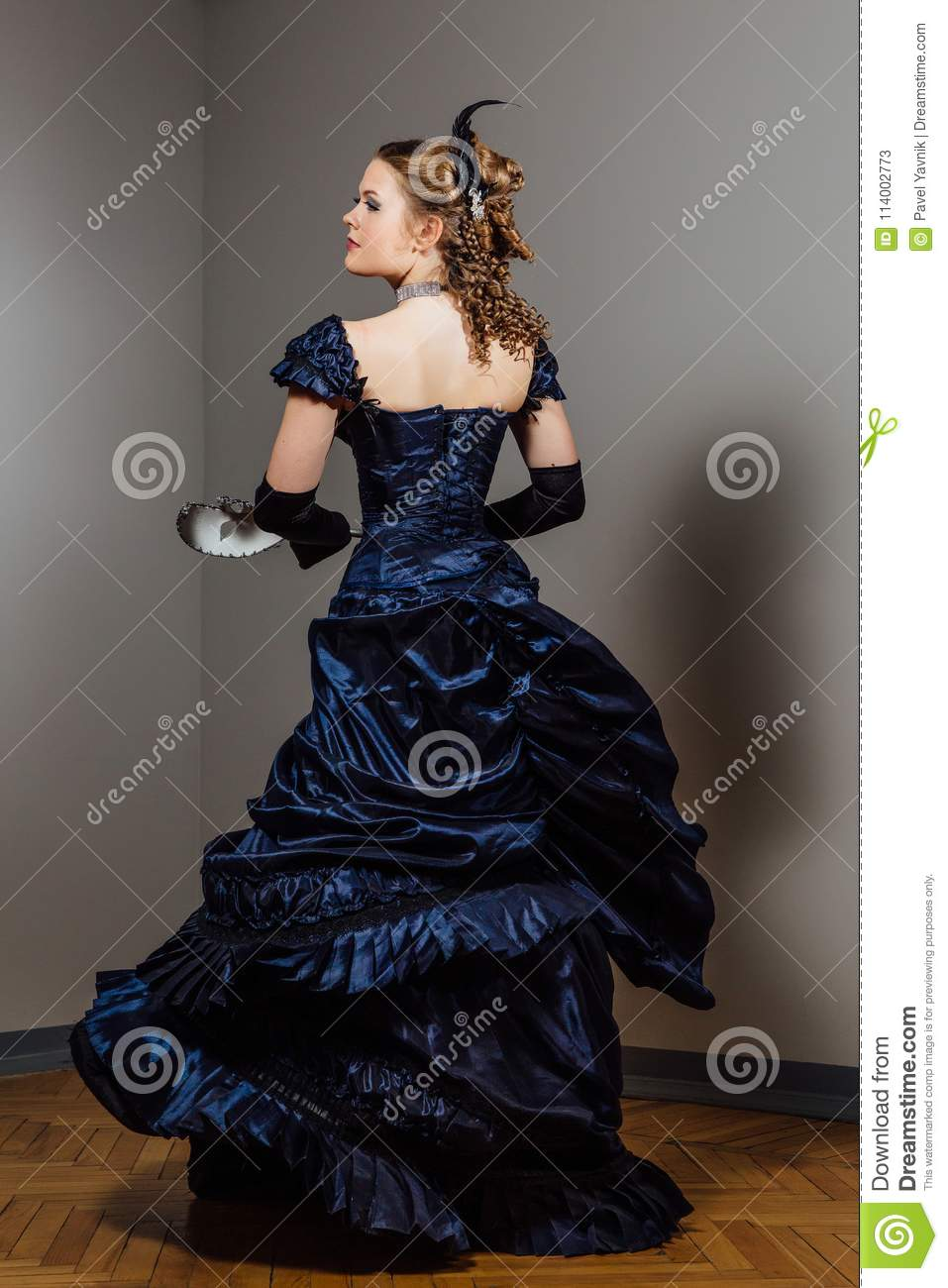 Girl in vintage blue dress with mask in hands. Actress in the role. Actor`s game.