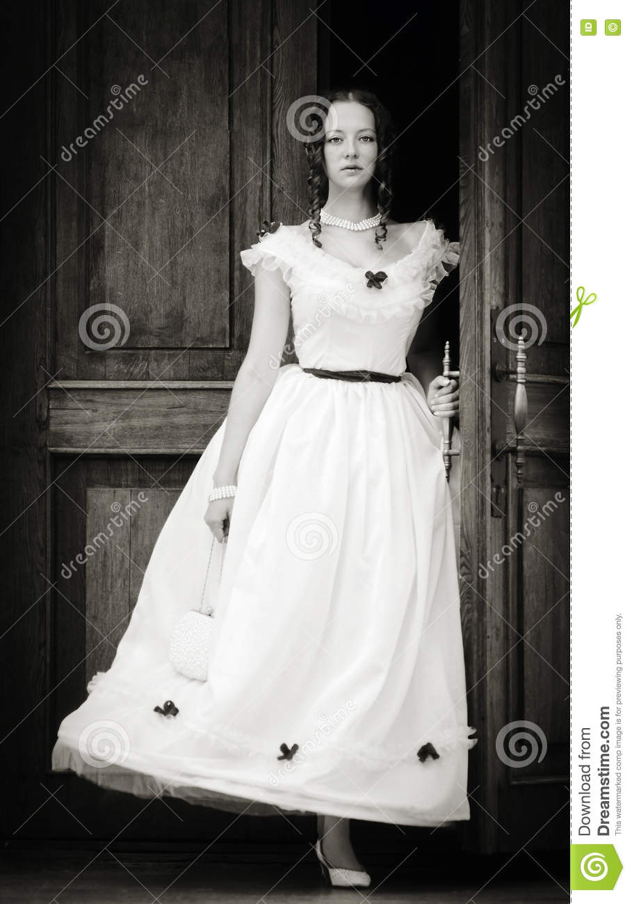Girl in a vintage dress coming out of doors