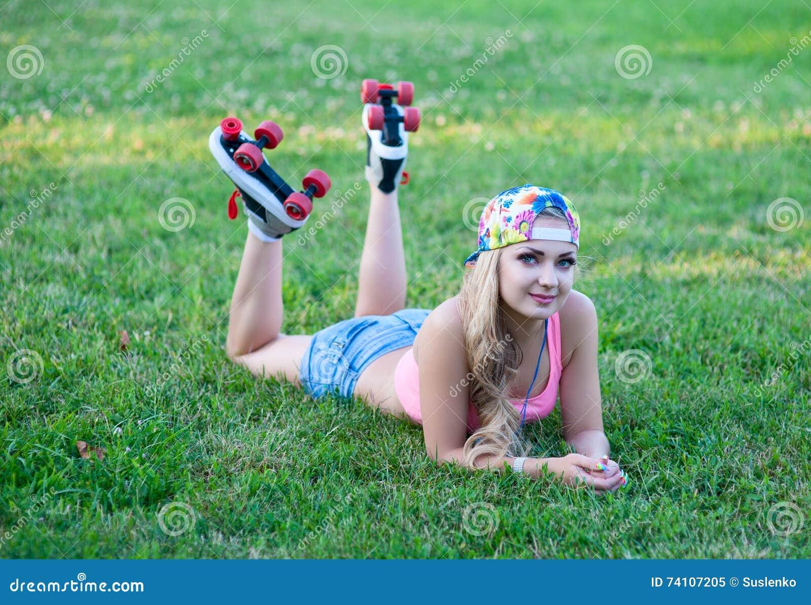 Girl On Vintage Roller Skates Lying On The Grass Stock
