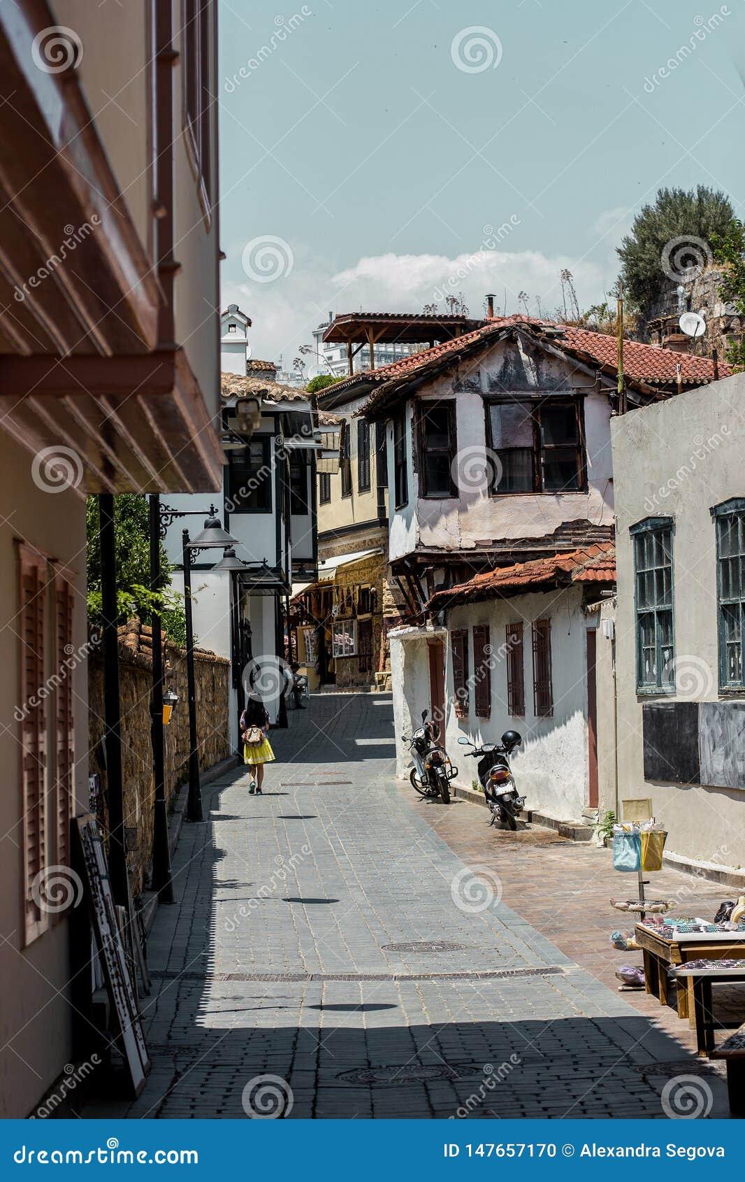 Girl walking down the sunny street of old town Kaleici, Antalya, Turkey