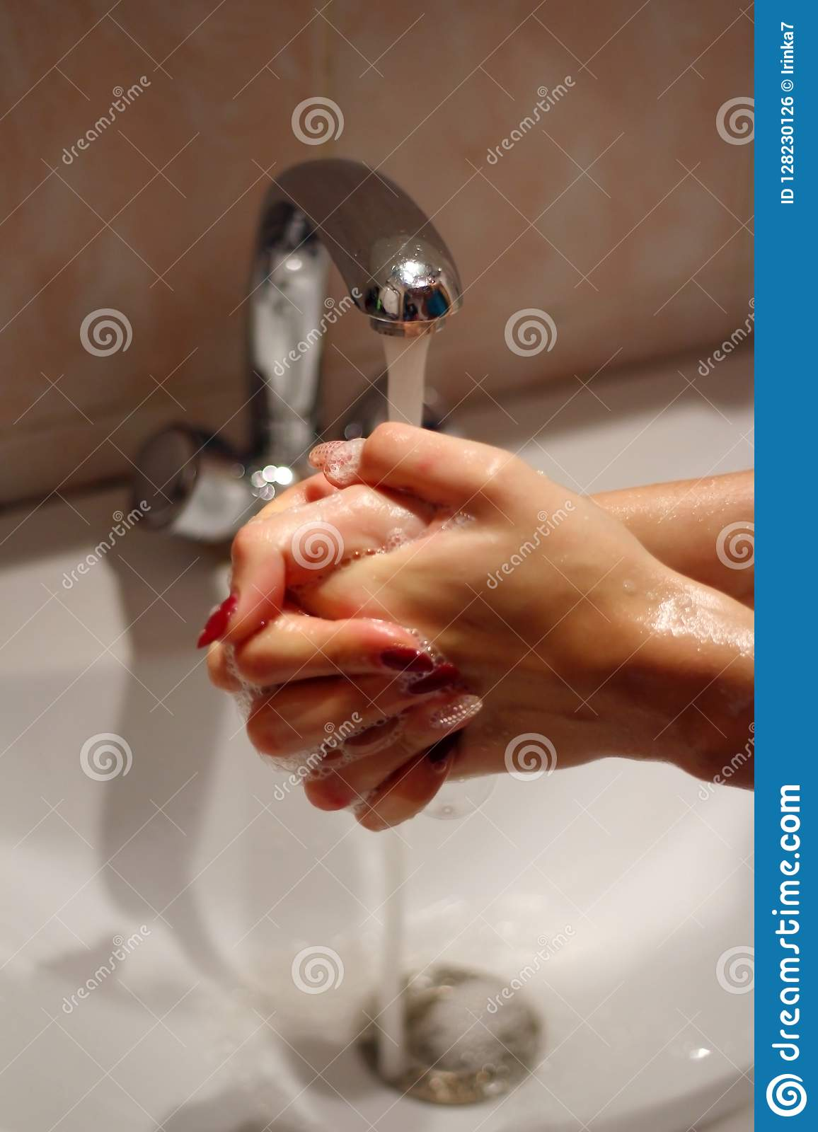 Girl washes her hands with soap under running water