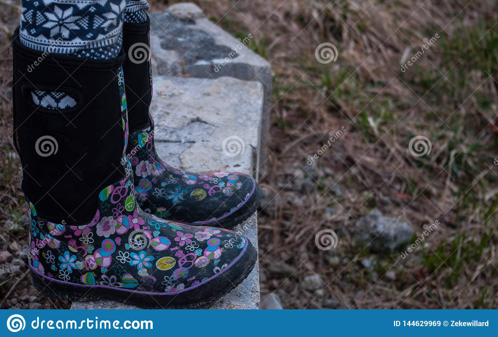 Girl wearing black rubber boots with pink designs