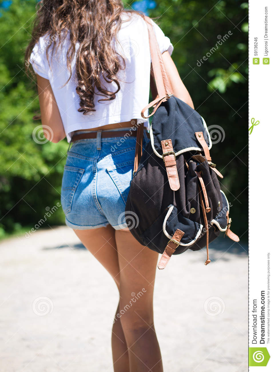 girl wearing jeans shorts with backpack walking stock
