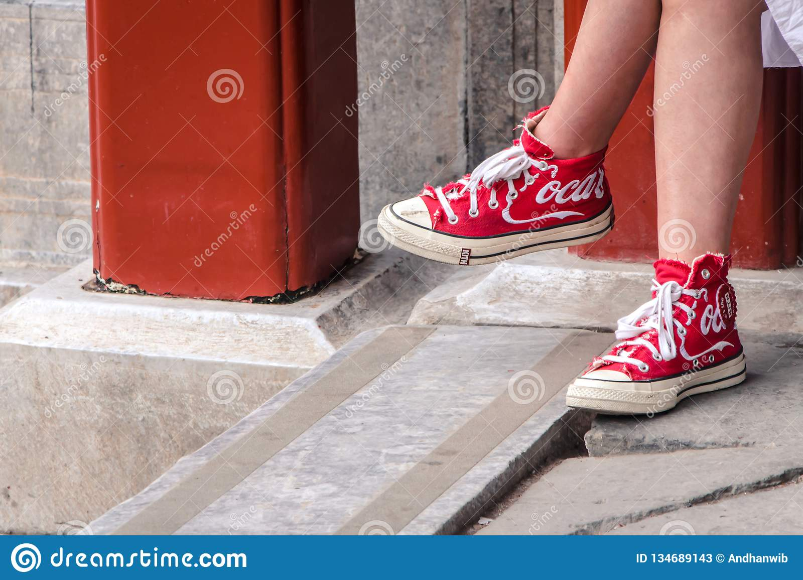 Girl Wearing Red Shoes with Coca Cola Logo on it