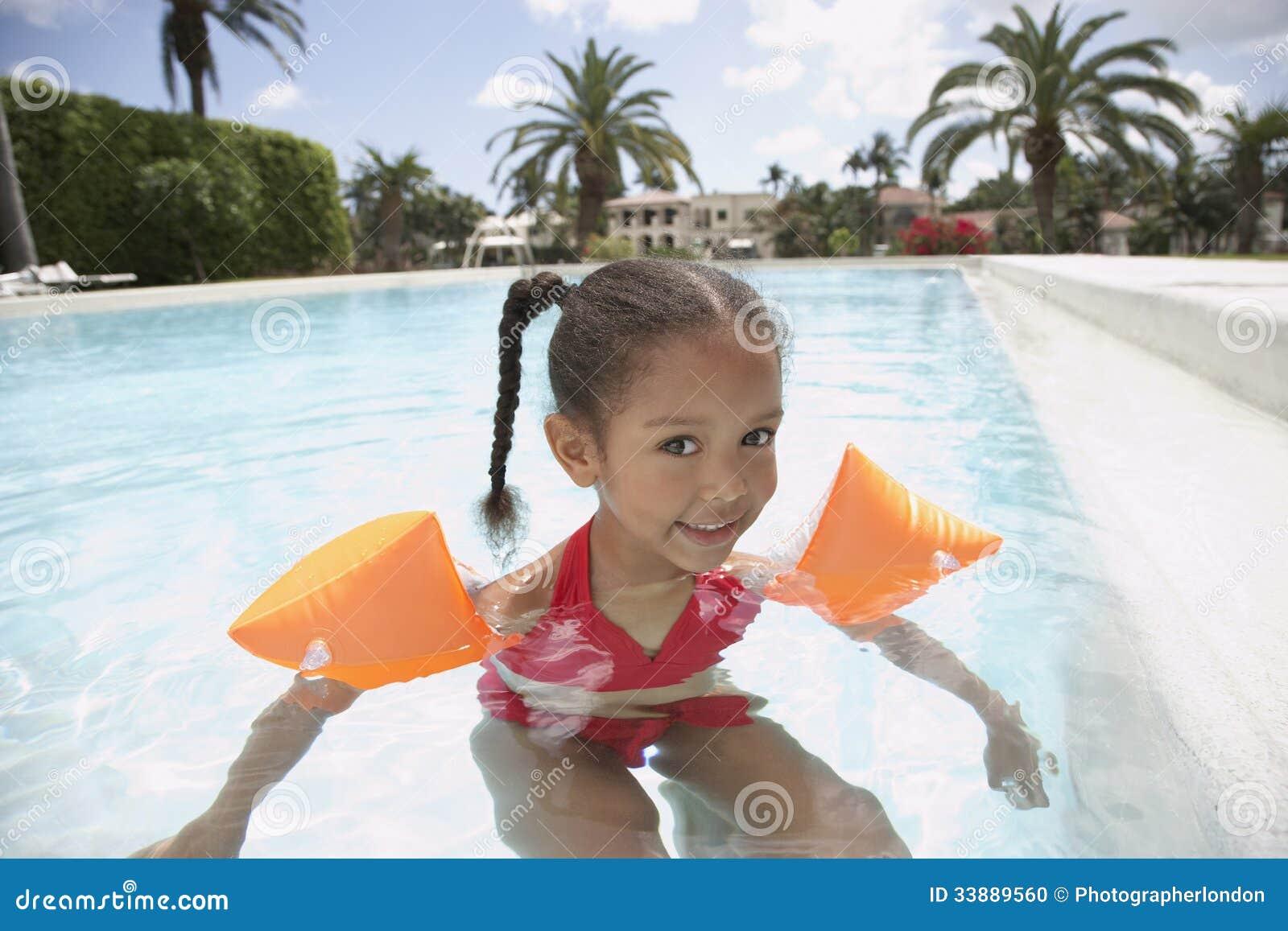 Swimming Pool Wings : Girl wearing water wings in swimming pool stock photo