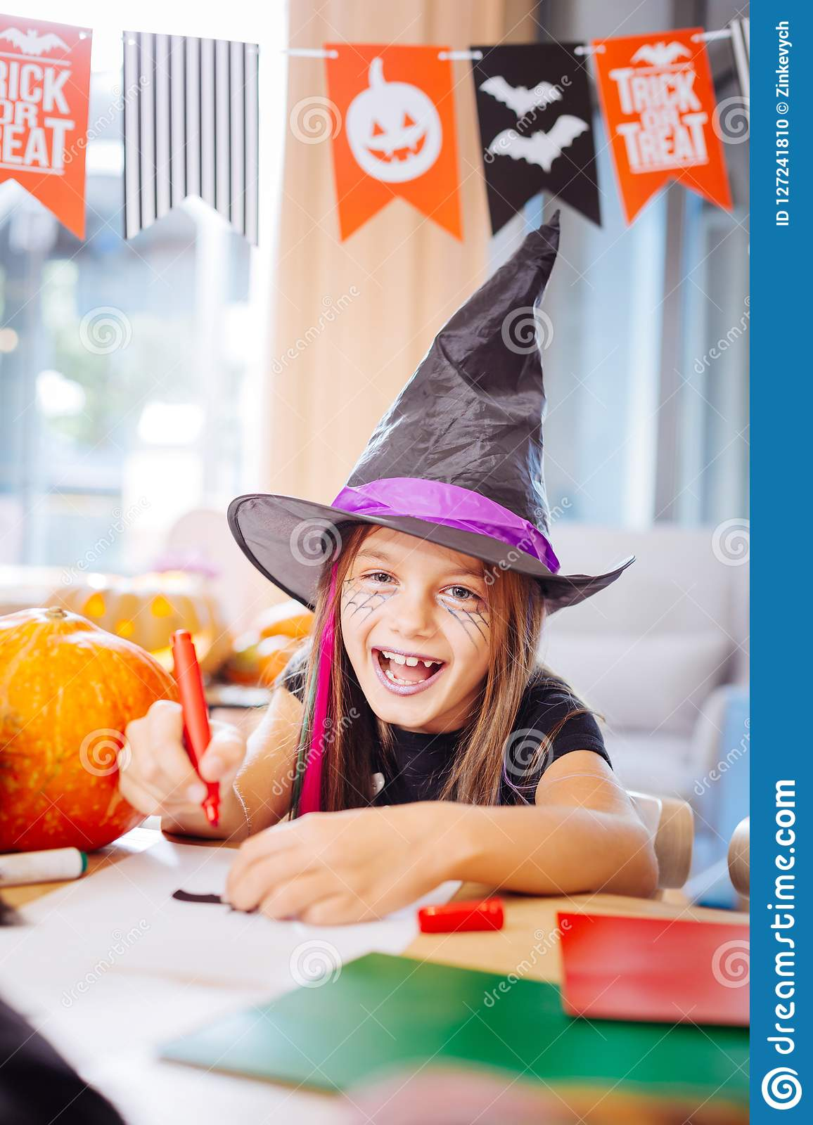 Girl wearing wizard Halloween costume laughing while drawing scary pictures