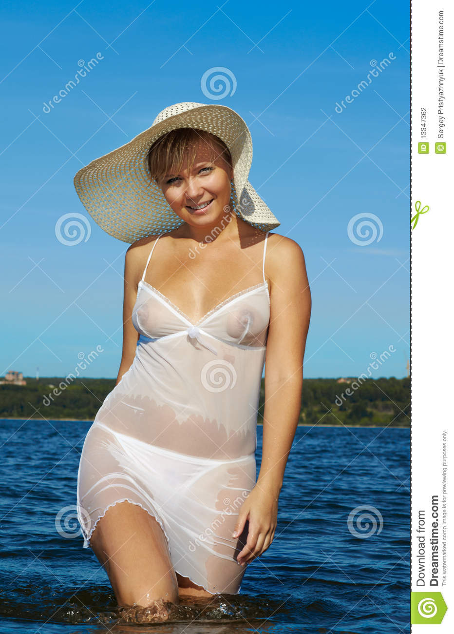 Beautiful blonde girl in wet peignoir and summer hat posing in the ...