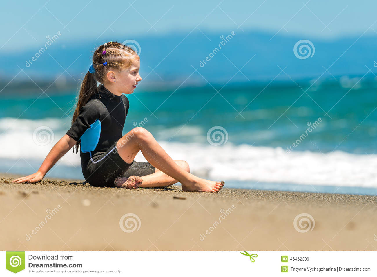9484608659 Girl in a wetsuit on the beach. Little girl sitting in a wetsuit on the