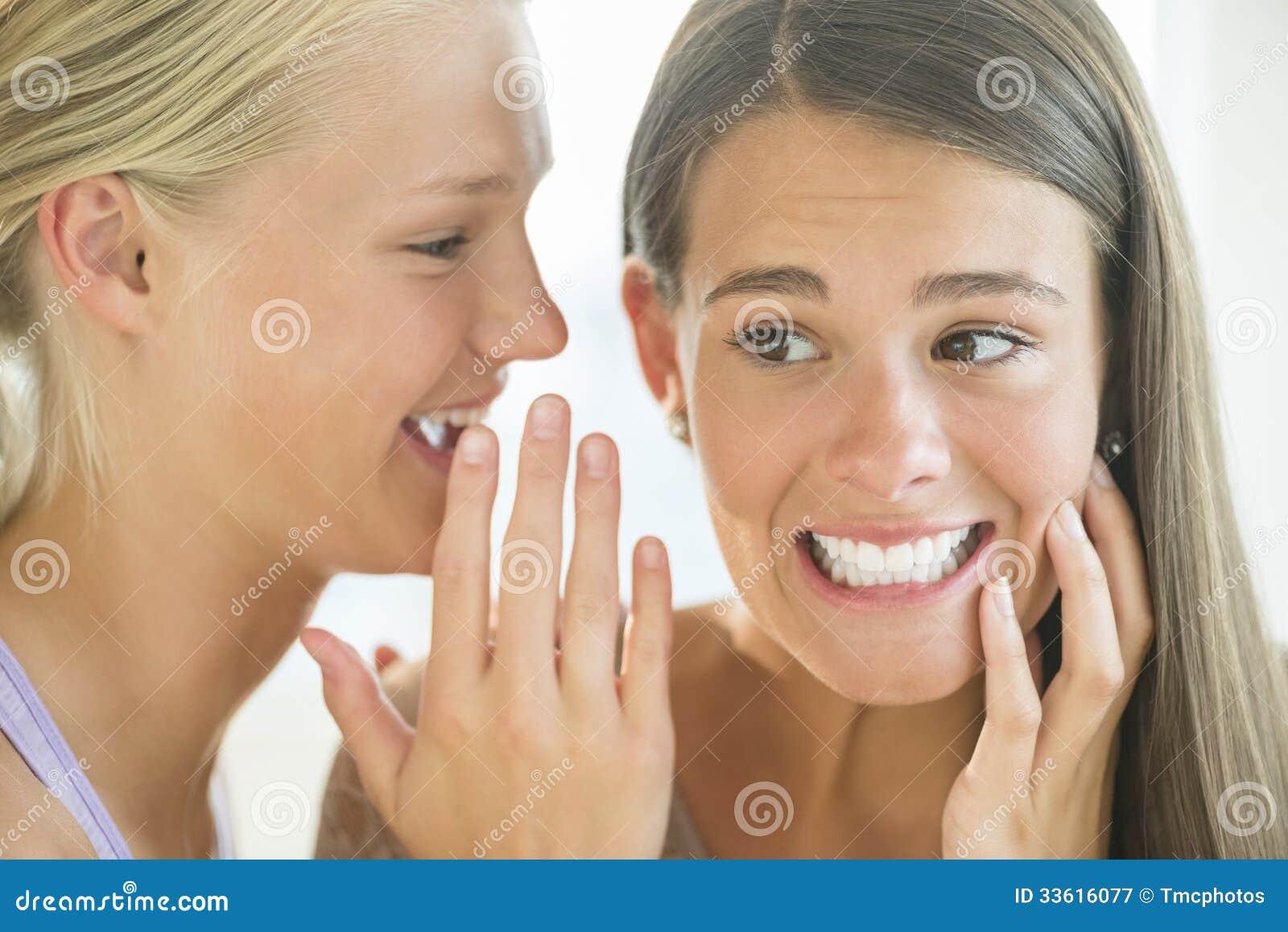 Girl Whispering Into Friend s Ear