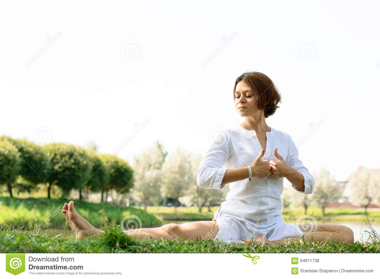 c8c3d93110f Girl In White Clothes Practicing Yoga At The River-bank Stock Photo ...