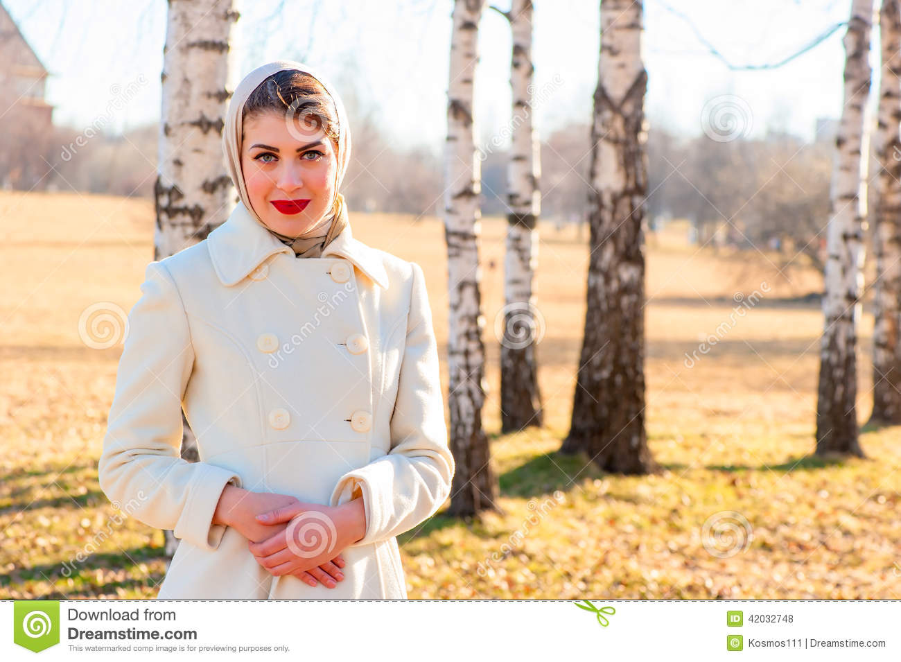 0a86128c210 Portrait of a girl in a white coat on the background of birch trees