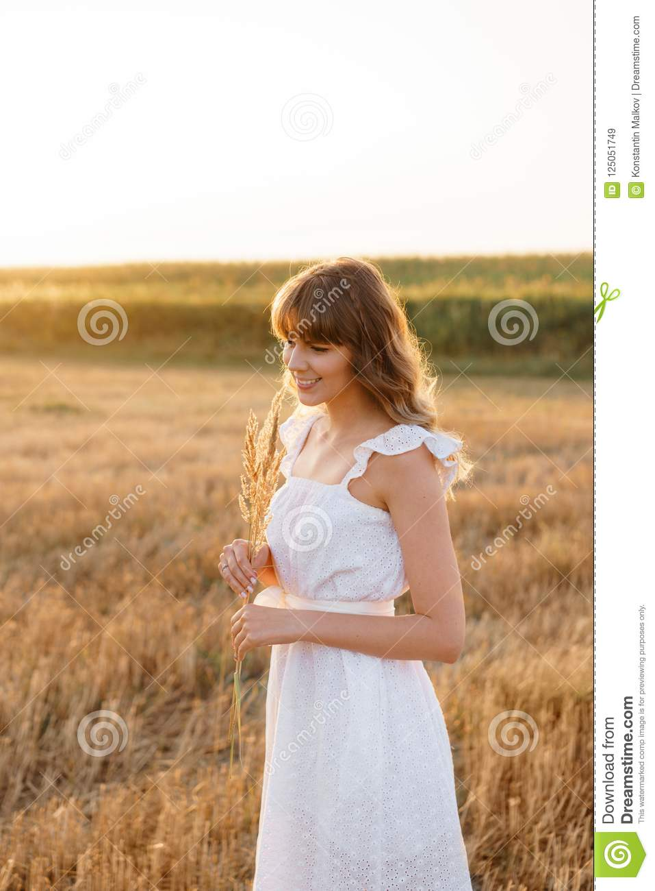 Girl in white dress with spikelets. Woman in field, place for text. Spike and girl in field. Late summer and early