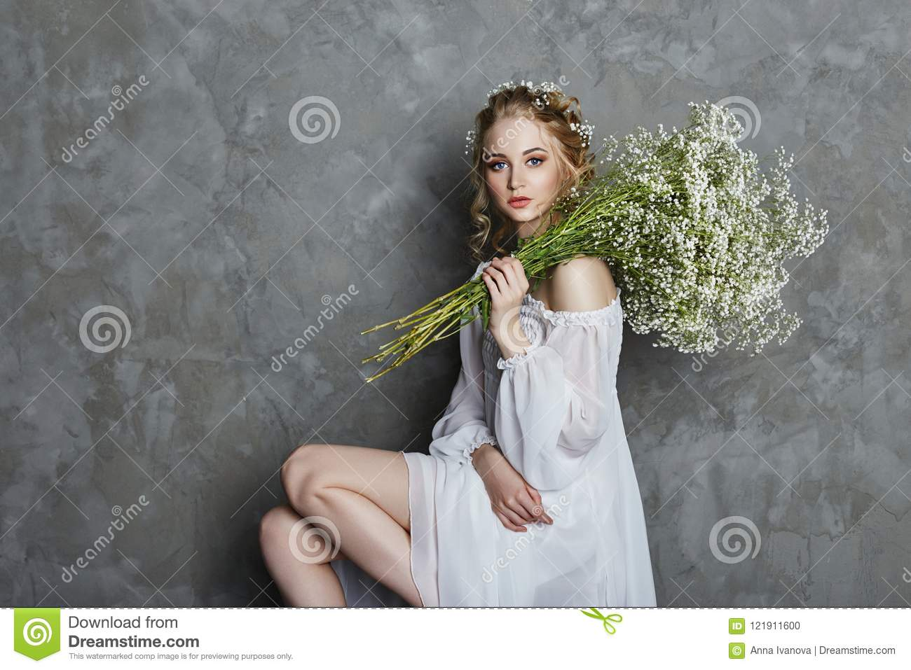 Girl white light dress and curly hair, portrait of woman with flowers at home near the window, purity and innocence. Curly blonde