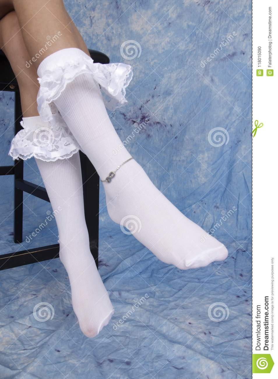 Close Up Of Girls Legs Wearing White Ruffled Socks And Silver Ankle Chain