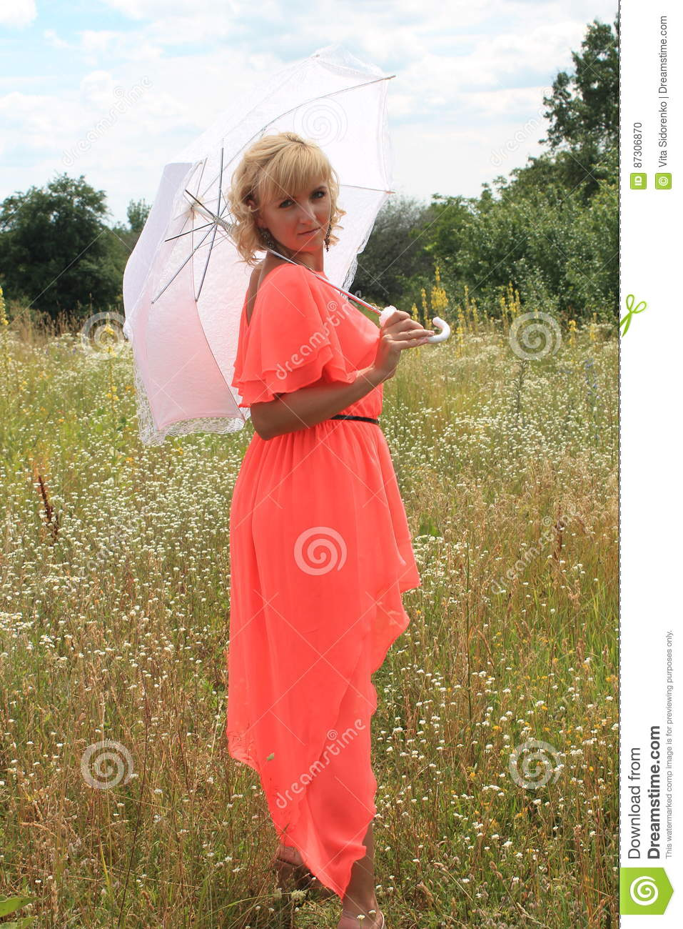Girl with a white umbrella, a long dress, a field of flowers, a pink dress. beautiful blonde girl in a field of flowers