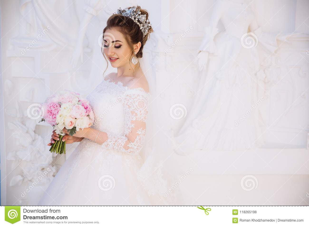 A Girl In A White Wedding Dress With Lace Posing In A Snow White