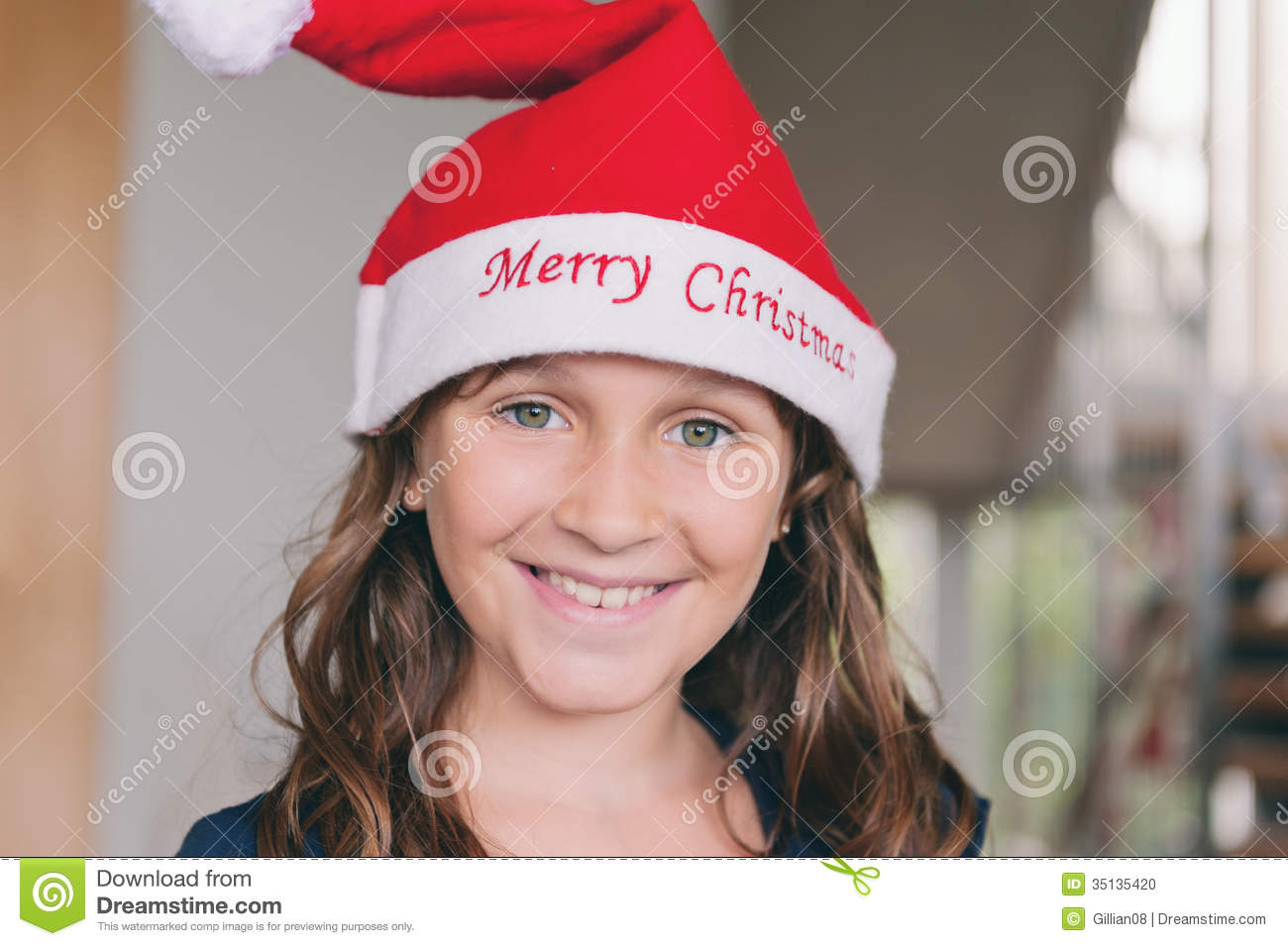 Girl wearing red hat with merry christmas embroidered across the brim