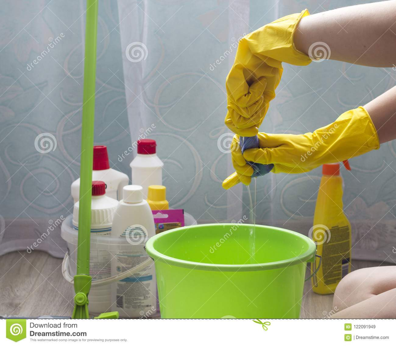A girl in yellow gloves squeezes a rag into a bucket domestic