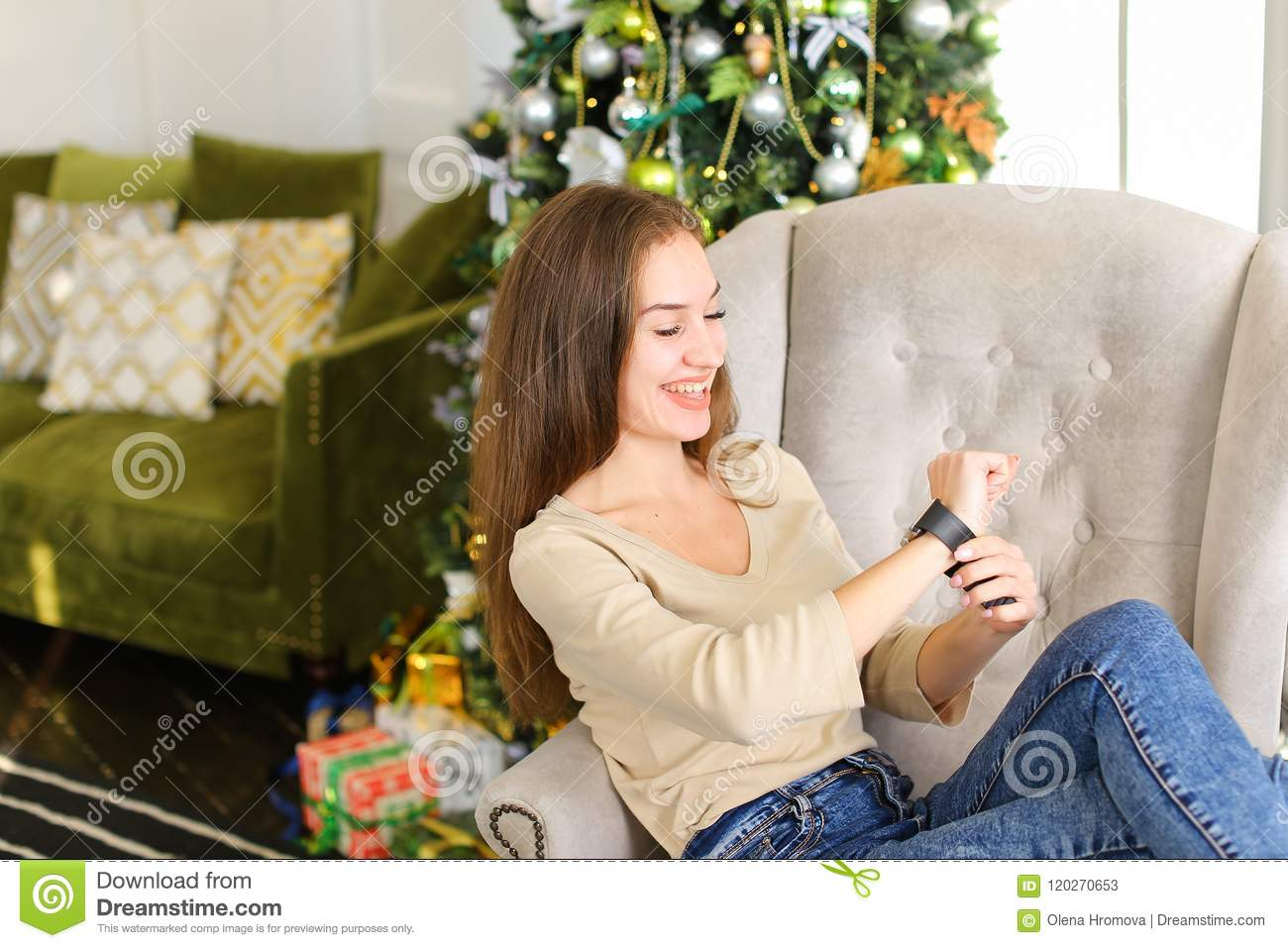 girlfriend get smartwatch from boyfriend as present for new year smiling lady sitting in chair near pinetree with gift on hand fair haired girl with neat