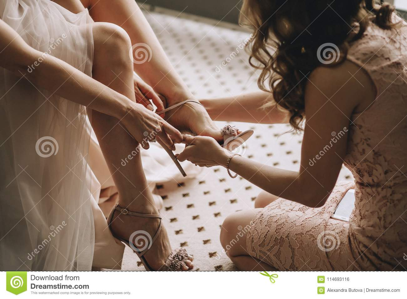 A girlfriend helps a bride to put on her wedding shoes. Beautiful female legs closeup