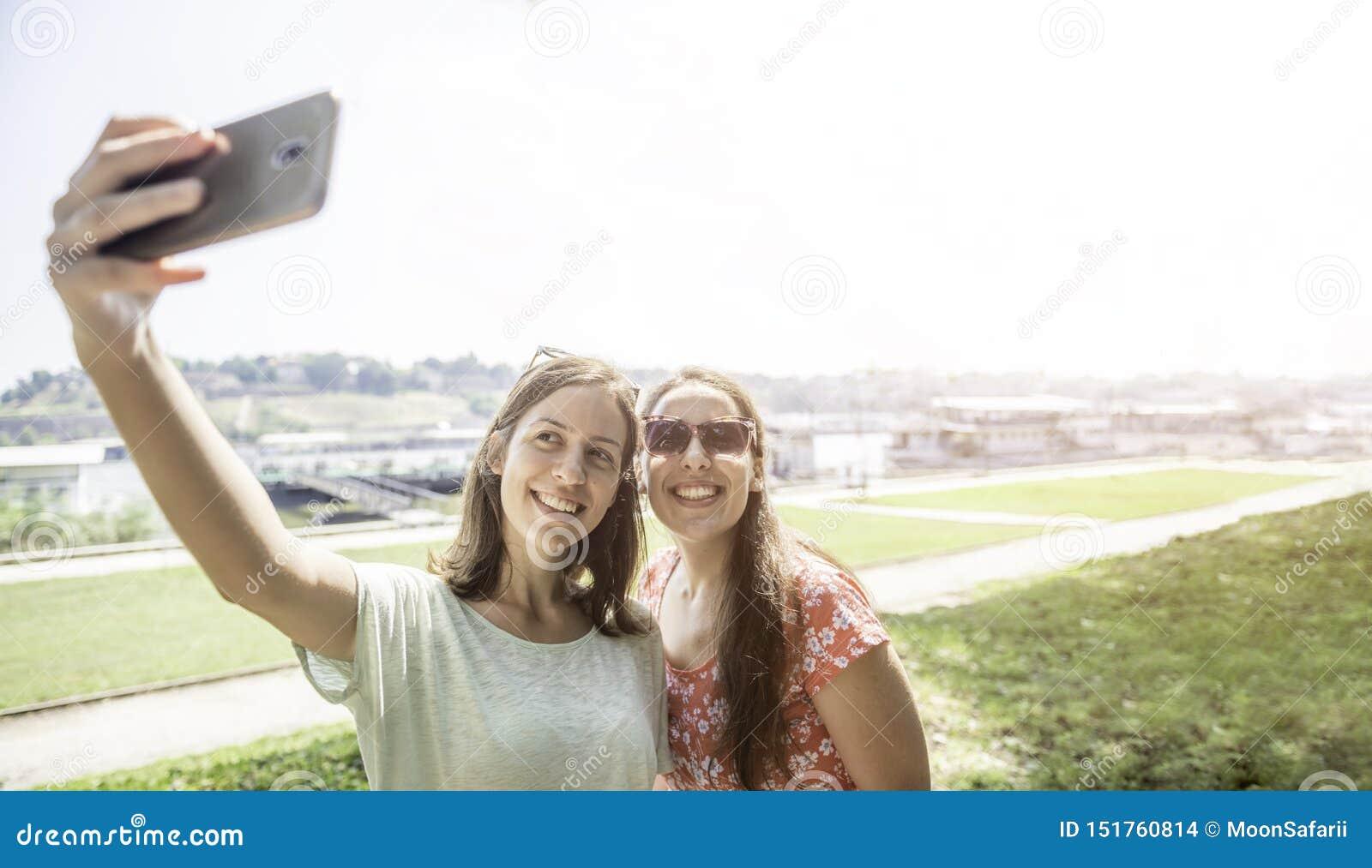 Girlfriends taking selfie together having fun outdoors concept of modern women friendship lifestyle female best friends happy