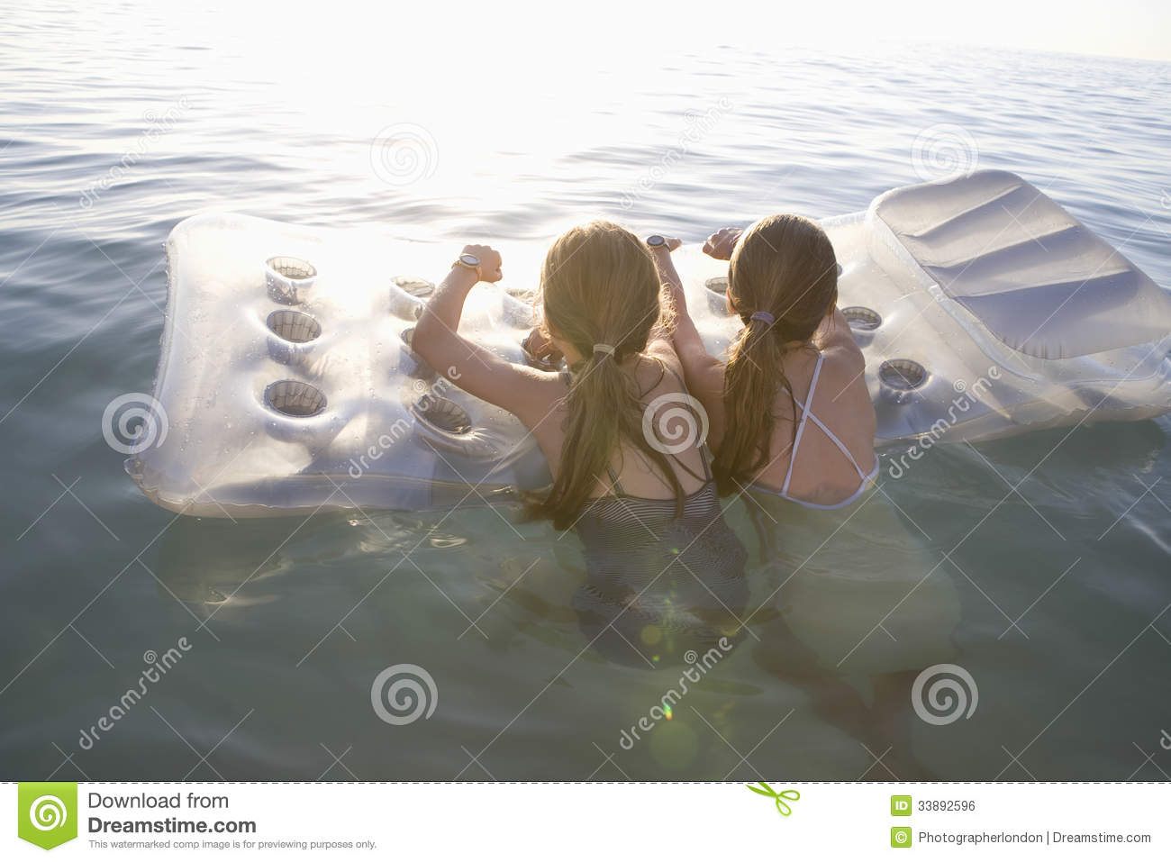 Girls On Air Mattress Floating On Water Stock Photo