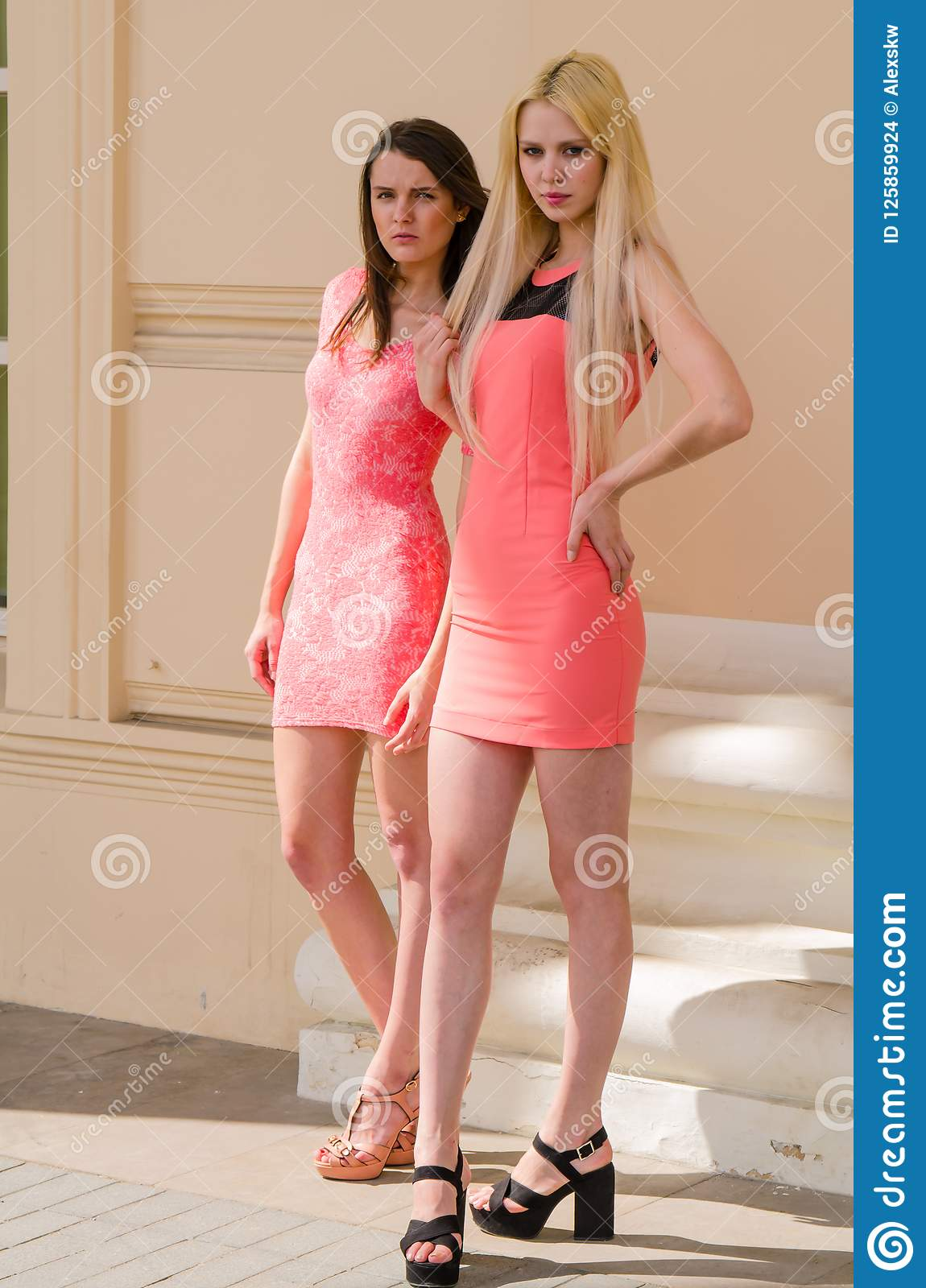 8f2dcfbe Girls, Blonde And Brunette, In Short Pink Dresses Stand In The Arch old  Stone Building With Large Columns Stock Photo - Image of contemplate, ...